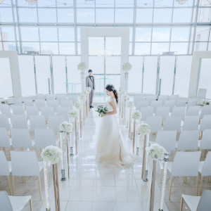 階段を上がると、白を基調としてセレモニースペースが広がる。 窓から差し込む自然光に包まれて、笑顔溢れる挙式が叶います。|グランドニッコー東京 台場の写真(5315650)