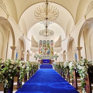 22M続くロイヤルブルーのバージンロードと11Mの天井高は、ウエディングドレスを引き立ててくれると話題。120年以上の時を刻むステンドグラスが輝く独立型の教会。 アニヴェルセル 長野の写真(5887636)
