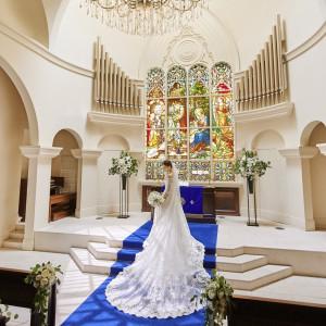 英国から受け継いだアンティークのステンドグラスが輝く大聖堂は、幼い頃に夢見た憧れの教会そのまま。アニヴェルセル長野オリジナルのウエディングドレスも根強い人気。 アニヴェルセル 長野の写真(5886555)