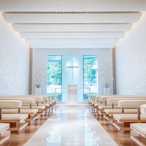 水中に雪が降り積もるような、神秘の世界をイメージ。自然光が差し込む明るいチャペルは、壁一面にはギリシャの白大理石タソスホワイトを、聖壇には真珠貝をあしらった純白の空間です|コンラッド東京の写真(7563028)