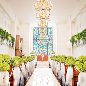 自然光を受けて輝くステンドグラスが、大理石のバージンロードに映り込む!神聖な輝きに包まれよう