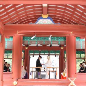 鮮やかな朱色の舞台でお互いに指輪を交換。 挙式の素敵な場面のひとつです。|鶴岡八幡宮(チアーズブライダルプロデュース)の写真(683220)
