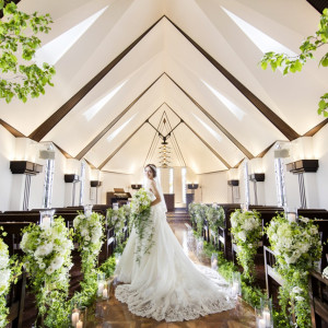 木目調のバージンロードに広がるウェディングドレスがよく映えるチャペル。自然光が柔らかく差し込むなか、スモーキーグリーンとウェディングホワイトの花に囲まれる幸福感を感じて。|felizcreer(フェリスクレール)の写真(1112580)
