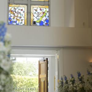 4人の天使が見守るステンドグラス。ご新婦様のご入場とともに開かれる扉。後ろには緑が広がりウエディングドレス姿をより美しく引き立ててくれます。|ルーデンス立川ウエディングガーデンの写真(913278)