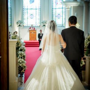 深紅のウエディングロードは生まれてから今までの「花嫁の人生」を表す。人生を振り返り、感謝の気持ちをかみしめて歩く。|ローズガーデンクライスト教会の写真(2157253)