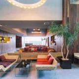 水と光と緑が融合する温もり溢れるウェイティングスペース。広島出身の建築家 谷尻誠氏によるデザインが原生林に自然と溶け込む。ブックディレクター幅充孝氏が手掛ける本棚も注目。