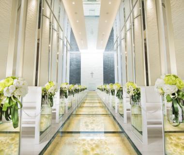 白バラとクリスタルが敷き詰められたガラスのバージンロード。祭壇には水が流れ、おふたりをより美しくみせるこだわりが詰まったチャペル
