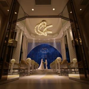 当館では夕方~夜の挙式もお受けしております。大きな窓から見上げる夜空と、館内のシャンデリアのあたたかな光が調和して幻想的な空間が広がります。|ヴォヤージュ ドゥ ルミエール ~Chatan Resort~の写真(611352)