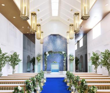 ウォーターカーテンの祭壇に、純白のドレスがまばゆく映えるブルーのバージンロード。祭壇を流れる水が光を受けてきらきらと輝き、幻想的なシーンを描きます。