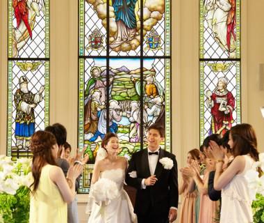 祭壇の奥に佇むステンドグラスからの光はより花嫁を美しく演出