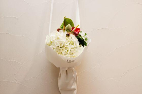 (撮影:編集部)  白のアジサイを主役にした花束。 個性的な形のパフィオペディルム(蘭)とアンスリウムを投入することでかわいくなりすぎず、スタイリッシュなイメージに。  <使用花材>アジサイ、パフィオペディルム、アンスリウム、ポリシャス(葉物)